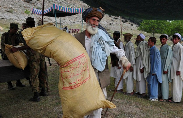 An elderly displaced man carries a sack of rations on his shoulder in northern Pakistan. Credit: Ashfaq Yusufzai/IPS