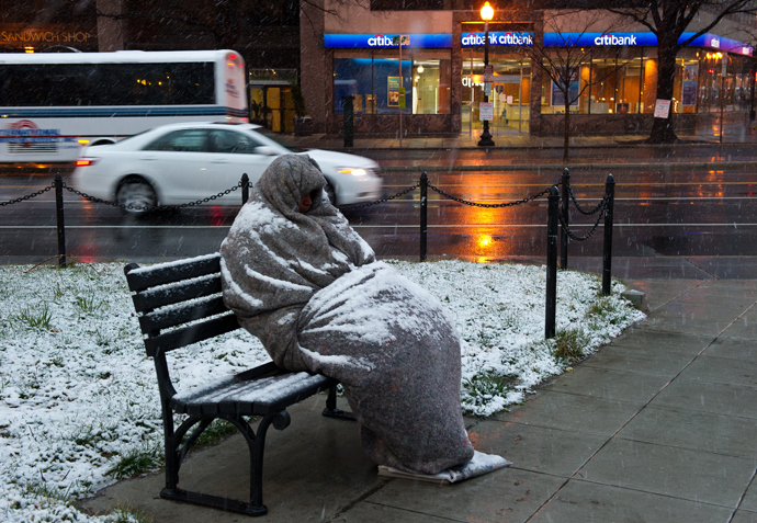 A homeless man sits covered in snow early in Washington, DC. (AFP Photo / Karen Bleier)