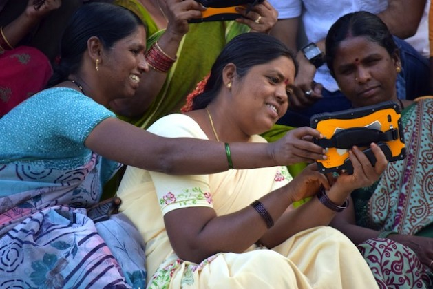 Members of a women-farmers' collective demonstrate use of a devices that sends daily bulletins on weather patterns, crops and other matters of importance to farming communities in rural India. Credit: Stella Paul/IPS