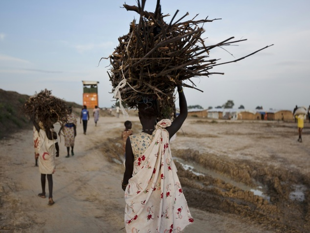 A young woman carries firewood after returning to the United Nations base outside Bentiu