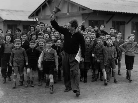 11th January 1939: A camp leader ringing the dinner bell at a camp for young Jewish refugees from Germany and Austria, at Dovercourt Bay near Harwich (Fox Photos/Getty Images)